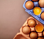 Horizontal closeup shot with two colorful cardboard containers of pink and violet color with chicken eggs, two egg yolks open and visible.
